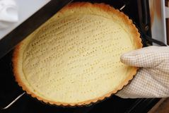 Förberedelse som bakar pajen Händer för man` s sätter formen med smeten ut ur ugnen Laga mat som är processaa Royaltyfri Bild