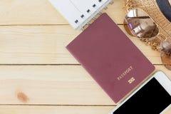 Förberedelsen för resande begrepp, passet, smartphonen, solglasögon, noterade boken, hatt på en träbakgrund Fotografering för Bildbyråer
