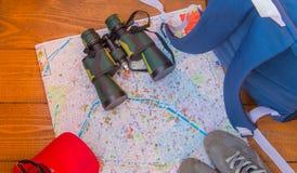 Förberedelsen för turen, lopp, ryggsäck, kikare, kamera, översikt på träbakgrund arkivfoto