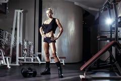 Förbereder sig den blonda flickan för kondition för att öva med hanteln i idrottshall arkivfoto