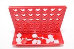 Förbind lek fyra med hjärta formade hål som isoleras på vit bakgrund. Arkivfoton