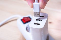 Förbinda en vit USB kabel till en vit USB uppladdare som pluggas in i en maktremsa Arkivfoto