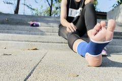 Förbinder kvinnlig användande resår för handen med ben, kvinnligt sätta förbinder på hennes sårade fot från sport royaltyfria foton