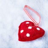 Förbindlig hjärta för röd leksak på en frostig vit snövinterbakgrund Förälskelse- och St-valentinbegrepp Arkivbilder