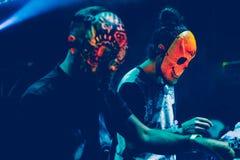 Förbluffa Djs med maskeringen som spelar blandande musik på sommar, festa festivalen Royaltyfria Foton