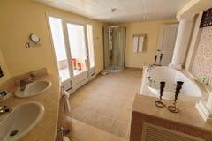 Förbluffa inviterande sikt av det inre moderna stilfulla badrummet Arkivfoto