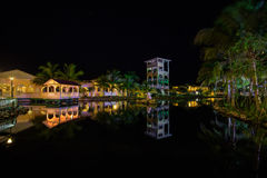 Förbluffa inviterande sikt av jordning för minnesCaribe hotell som tänds med olika varma ljus, reflekterade i vatten på aftontid  Fotografering för Bildbyråer