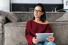 Förbluffa kvinnan inomhus i hem genom att använda minnestavladatoren fotografering för bildbyråer