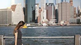 Förbluffa panorera skottet av den lyckliga europeiska kvinnan med flyghår som promenerar berömd horisont för Manhattan öflodstran lager videofilmer