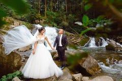 Förbluffa romantisk sikt av den lyckliga bruden med brudgummen nära den härliga storslagna vattenfallet i berg Lyxig bröllopsklän royaltyfri bild