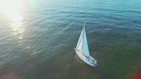 Förbluffa sikt av att segla yachten i det öppna havet på solnedgång Gr?nt hav med solreflexioner Surrsikt - f?glar synar h?g vink arkivfilmer