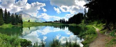 Förbluffa sikt av en liten bergsjö, spegeleffekt royaltyfria bilder