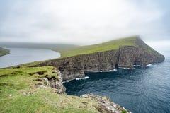 Förbluffa sikt av illusionsjön på slav- berg av Tralanipan den branta klippan i den Vagar ön, Faroe Island, norr Atlantic Ocean, royaltyfri fotografi