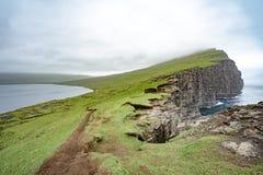 Förbluffa sikt av illusionsjön på slav- berg av Tralanipan den branta klippan i den Vagar ön, Faroe Island, norr Atlantic Ocean, royaltyfria foton