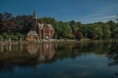 Förbluffa sjön som omges av grönska och gammal byggnad royaltyfri foto