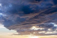 Förbluffa solnedgång med tungt mörkt - blåa moln arkivbild