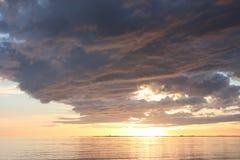 Förbluffa solnedgång med tungt mörkt - blåa moln royaltyfria bilder