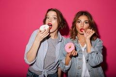 Förbluffa två kvinnavänner som äter donuts Arkivbilder