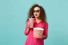 Förbluffad afrikansk flicka i exponeringsglas för imax som 3d håller ögonen på popcorn för håll för filmfilm, kopp av sodavatten  arkivfoto