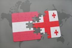 förbrylla med nationsflaggan av Österrike och georgia på en världskartabakgrund Arkivbild