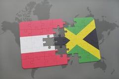 förbrylla med nationsflaggan av Österrike och Jamaica på en världskartabakgrund Royaltyfri Bild
