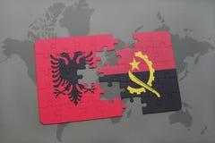 förbrylla med nationsflaggan av Albanien och Angola på en världskarta Royaltyfri Fotografi