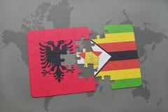 förbrylla med nationsflaggan av Albanien och Zimbabwe på en världskarta Arkivfoton