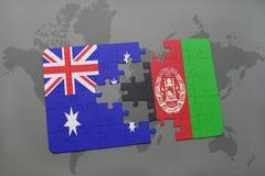 Förbrylla med nationsflaggan av Australien och Afghanistan på en världskartabakgrund Royaltyfri Bild