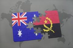 förbrylla med nationsflaggan av Australien och Angola på en världskartabakgrund Royaltyfri Fotografi