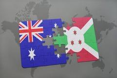 förbrylla med nationsflaggan av Australien och Burundi på en världskartabakgrund Fotografering för Bildbyråer