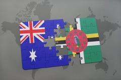 förbrylla med nationsflaggan av Australien och Dominica på en världskartabakgrund Fotografering för Bildbyråer