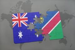 förbrylla med nationsflaggan av Australien och Namibia på en världskartabakgrund Arkivbilder