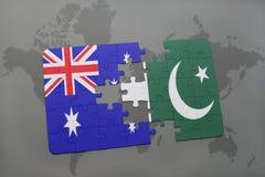 förbrylla med nationsflaggan av Australien och Pakistan på en världskartabakgrund Arkivfoton