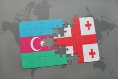 förbrylla med nationsflaggan av Azerbajdzjan och georgia på en världskartabakgrund Arkivbilder