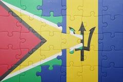 Förbrylla med nationsflaggan av Barbados och guyana Arkivfoto
