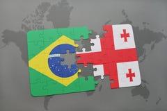 förbrylla med nationsflaggan av Brasilien och georgia på en världskartabakgrund Royaltyfria Bilder