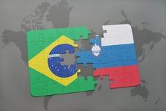 förbrylla med nationsflaggan av Brasilien och Slovenien på en världskartabakgrund Royaltyfri Foto