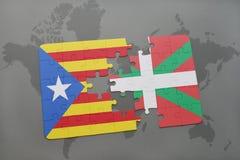 Förbrylla med nationsflaggan av catalonia och det basque landet på en världskartabakgrund Royaltyfri Bild