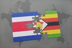 förbrylla med nationsflaggan av Costa Rica och Zimbabwe på en världskarta Royaltyfria Foton