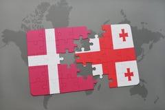 förbrylla med nationsflaggan av Danmark och georgia på en världskartabakgrund Fotografering för Bildbyråer