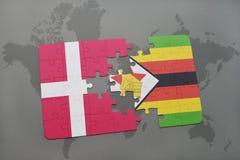 förbrylla med nationsflaggan av Danmark och Zimbabwe på en världskartabakgrund Fotografering för Bildbyråer