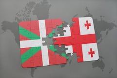 förbrylla med nationsflaggan av det basque landet och georgia på en världskartabakgrund Royaltyfria Bilder