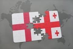förbrylla med nationsflaggan av England och georgia på en världskartabakgrund Royaltyfri Bild