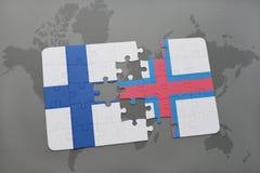 förbrylla med nationsflaggan av Finland och Faroe Island på en världskartabakgrund Arkivfoto