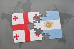 förbrylla med nationsflaggan av georgia och Argentina på en världskarta Arkivfoto