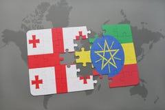 förbrylla med nationsflaggan av georgia och Etiopien på en världskarta Arkivbilder