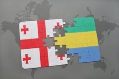 förbrylla med nationsflaggan av georgia och Gabon på en världskarta Arkivbild