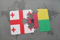 förbrylla med nationsflaggan av georgia och Guinea-Bissau på en världskarta Fotografering för Bildbyråer