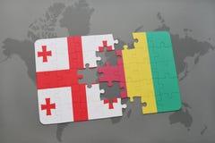 förbrylla med nationsflaggan av georgia och guineaen på en världskarta Royaltyfria Foton