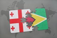 förbrylla med nationsflaggan av georgia och guyana på en världskarta Arkivbild